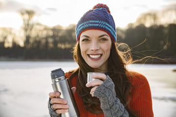 Portrait of smiling woman drinking hot beverage from thermos flask outdoors in winter