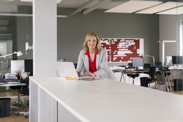 Portrait of smiling businesswoman using laptop in office