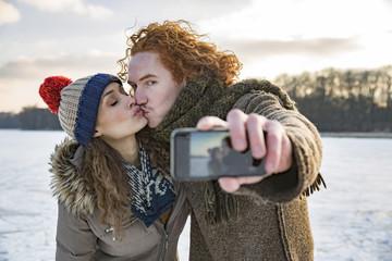 Couple kissing on frozen lake taking a selfie