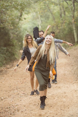 Four happy friends having fun on path in the forest