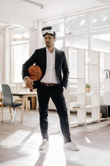 Businessman wearing VR glasses holding basketball in office