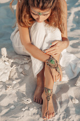 attractive bohemian style woman lying on the sand