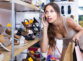 portrait of woman chatting on phone while picking new shoes in store