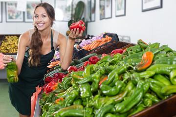 Seller holding fresh paprika in hands in supermarket
