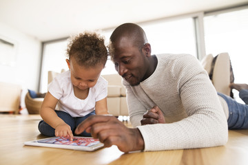 Afro-american father with little daughter with tablet at home.