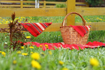 Fotobehang A wicker basket and a bright red napkins are in front of a hedge in the garden.