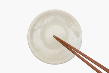 Traditional Japanese wooden chopstick on white ceramic plate