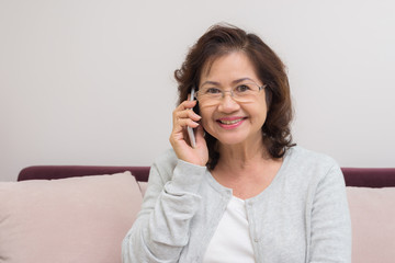 Asian senior woman cheerfully chatting with friends on mobile phone