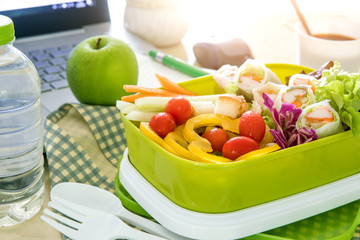 Close up the green Lunch box on work place of working desk ,Healthy eating clean food habits for diet and health care concept
