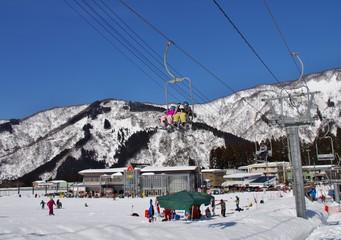 快晴のスキー場のリフトに乗る人たち