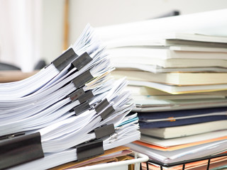 Many documents are on the desk.