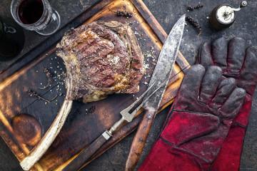 Barbecue Wagyu Tomahawk Steak als Draufsicht  auf einem verbrannten Schneidebrett