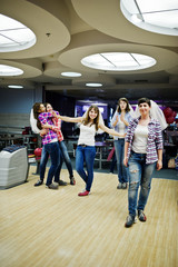 Group of girls having fun and play bowling at hen party.