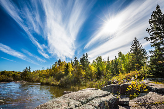 Incredible cirrus clouds  and huge flat stones in Old Pinawa Dam Park. Indian summer in Manitoba, Canada. The concept of ecological tourism