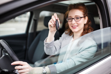 Car rental concept.Woman sitting in car and showing the keys.