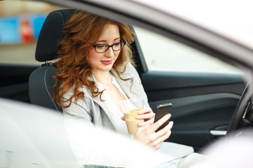 Attractive red hair businesswoman talking on the phone while waiting in the car.