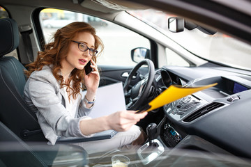 Attractive female sales manager using laptop and phone in the car.Preparing and looking into contract papers.