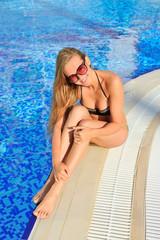 Sexy model in bikini near swimming pool with blue water