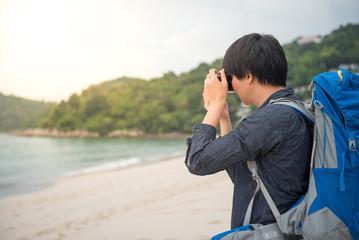 Young Asian backpacker man taking photos of beautiful tropical beach and sea by camera, background for summer holiday, vacation time or travel photography concepts