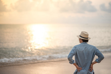 Young Asian man with jean shirt and hat standing on the beach and looking beautiful sunset, vacation time and summer holiday concepts