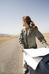 femme seule en voiture au milieu du désert qui cherche sa route sur une carte