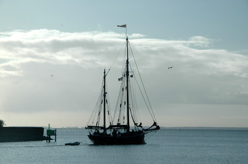 Silhouette of old sail ship leaving harbor.