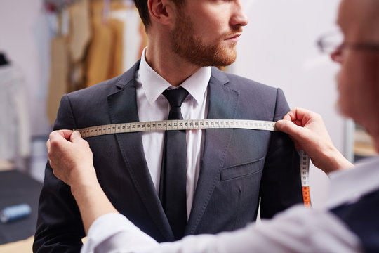Mid section portrait of tailor fitting bespoke suit to model