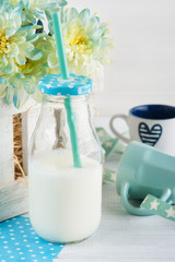 Bottle of milk with straw and blue cup