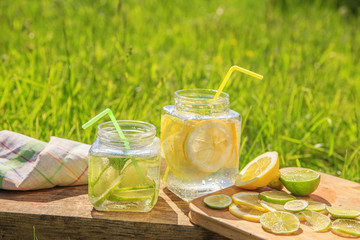 Lemon and lime slices in jars in summer wooden background.