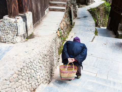 hunched old woman on street in Chengyang village