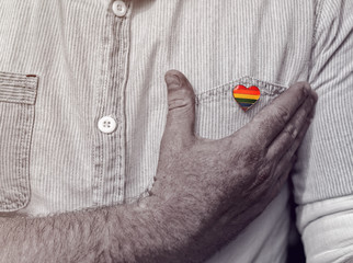 A rainbow flag in the shape of a heart is pinned to the shirt pocket. The man touches himself with his hand near the badge