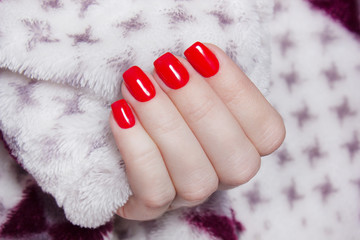 Red manicure. Hand in a warm blanket. wool Shaggy background