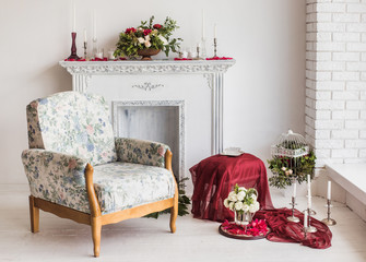 Beautiful interior in white and red colors with decorative fireplace, cozy armchair and floral compositions on wooden floor. Horizontal color photo.