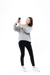 Smiling pretty girl standing and taking selfie on mobile phone