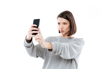 Pretty young girl taking selfie on mobile phone