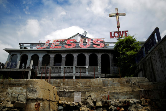 """Signs reading """"Jesus"""" and """"Love"""" sit on a dilapidated building near the Taunton River in Somerset"""
