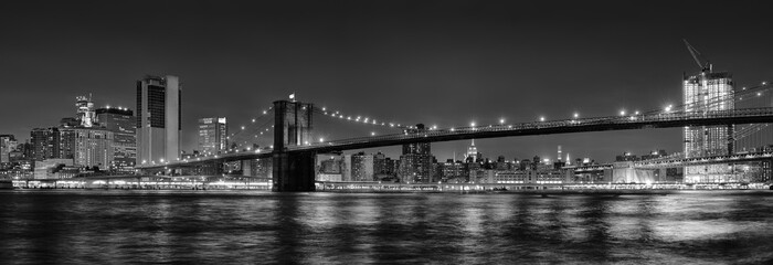 Black and white panoramic photo of Brooklyn Bridge at Night, NYC.