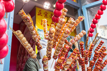 Foto op Plexiglas Beijing stall with caramelized fruit on stick on street