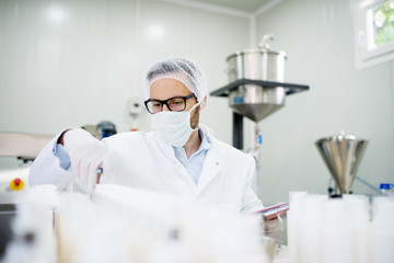 Young technologist making face care creams. Sitting in a cosmetic products factory.