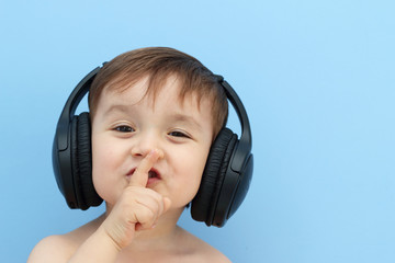 child with headphones, silence gesture