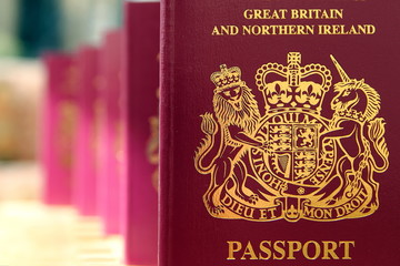 Five British United Kingdom European Union Biometric passports queueing in a line in shallow focus