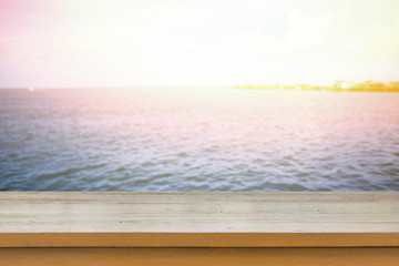 Empty top of wooden table or counter and view of tropical beach.