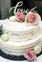 Beautiful wedding cake with cream With text Love on top pink flowers roses