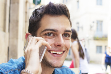 portrait of young man modern talking on mobile phone smiling