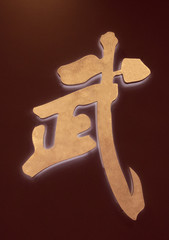 Chinese symbol in gold orange for martial or power, as in martial arts, against  a dark maroon background.