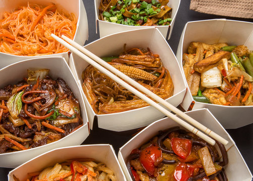 Chinese food in different cardboard boxes and wooden sticks
