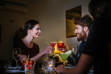 Happy young couple making a toast with cocktails on night out
