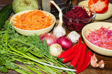 Raw ingredients for cooking vegetarian soup on a wooden table, top view.
