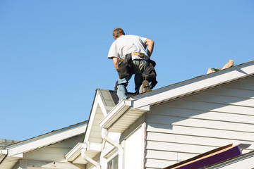 Worker installing new roof on home