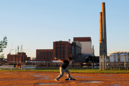 A softball team warms up on a field beside the Mystic Generating Station power plant in Charlestown